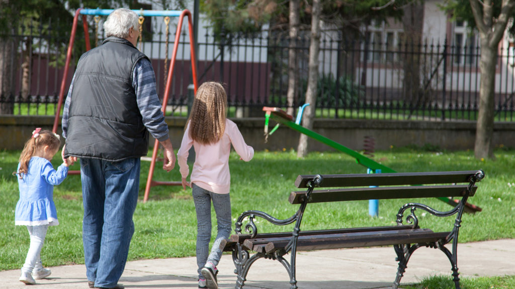 Senior man is taking his granddaughter to the playground on a sunny spring day. Copy space shot.