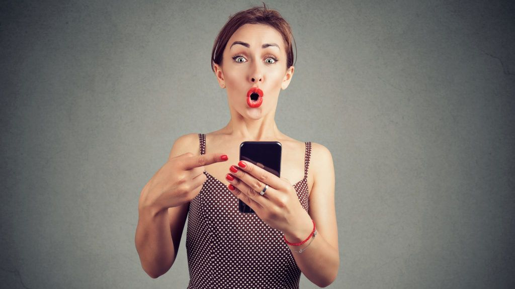 Shocked ironic girl holding smartphone and pointing at it sunned with breaking news
