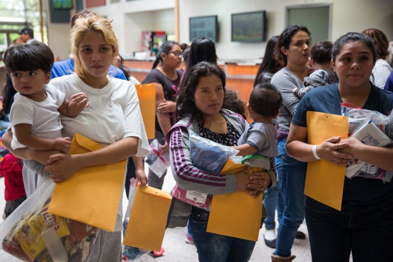 """(FILES) In this file photo taken on June 17, 2018 immigrants wait to head to a nearby Catholic Charities relief center after being dropped off at a bus station shortly after release from detention through """"catch and release"""" immigration policy in McAllen, Texas.  A US judge on July 9, 2018 gave the government more time to reunite migrant children aged five or younger with their parents separated as a consequence of a """"zero tolerance"""" policy, US media reported.  / AFP PHOTO / Loren ELLIOTT"""