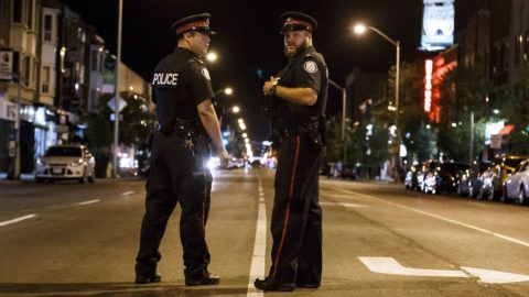 Toronto Police officers stand watch at the foot of Danforth St. at the scene of a shooting in Toronto, Ontario, Canada on July 23, 2018.  A gunman opened fire in central Toronto on Sunday night, injuring 13 people including a child. Two dead incluiding gunman, police reported. / AFP PHOTO / Cole BURSTON