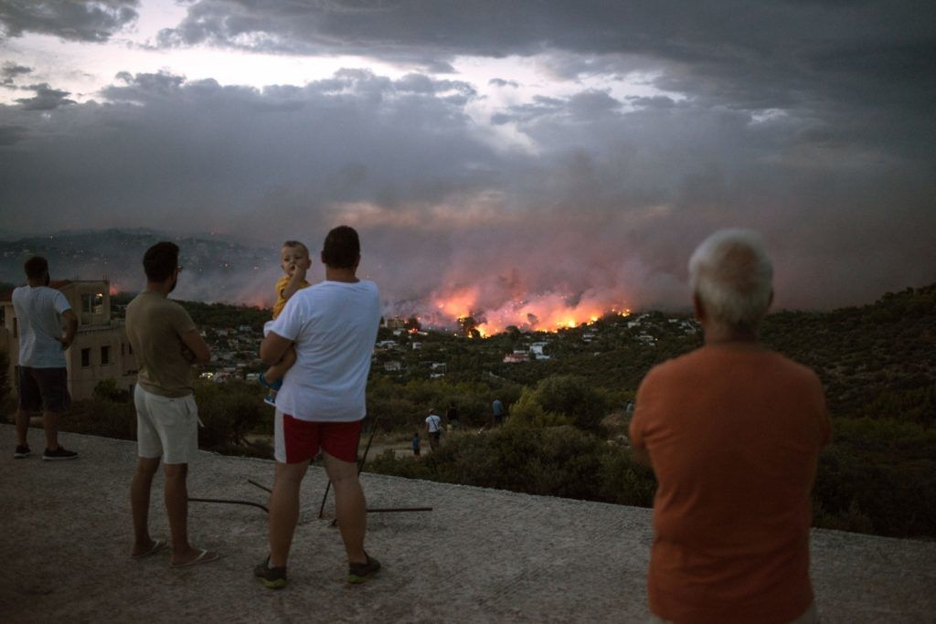 """People watch a wildfire in the town of Rafina, near Athens, on July 23, 2018.  At least 20 people have died and more have been injured as wild fires tore through woodland and villages around Athens on Monday, while blazes caused widespread damage in Sweden and other northern European nations. More than 300 firefighters, five aircraft and two helicopters have been mobilised to tackle the """"extremely difficult"""" situation due to strong gusts of wind, Athens fire chief Achille Tzouvaras said.   / AFP PHOTO / ANGELOS TZORTZINIS"""