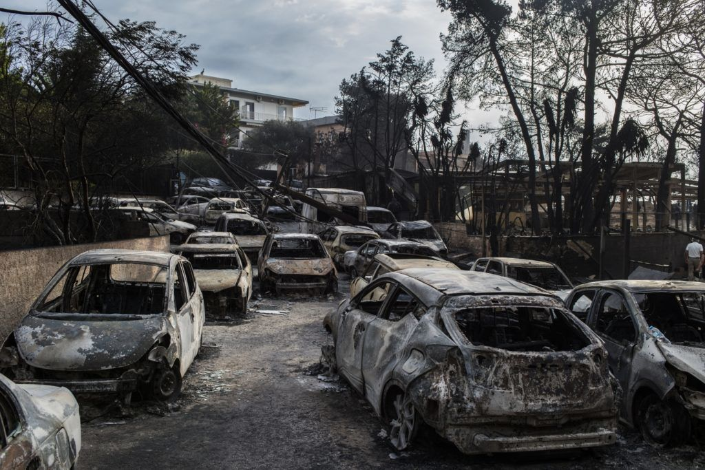 This photo taken on July 24, 2018 show cars burnt following a wildfire at the village of Mati, near Athens, on July 24, 2018. Fifty people have died and 170 have been injured in wildfires ravaging woodland and villages in the Athens region, as Greek authorities rush to evacuate residents and tourists stranded on beaches along the coast on July 24, 2018. The death toll soared with a Red Cross official reporting the discovery of 26 bodies in the courtyard of a villa at the seaside resort of Mati.  / AFP PHOTO / ANGELOS TZORTZINIS