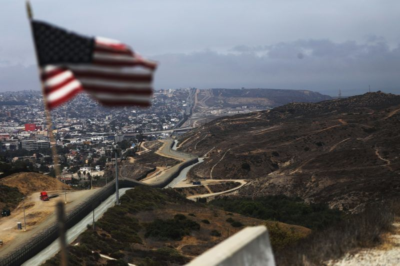 SAN DIEGO, CA - JULY 16: An American flag flies along a section of the U.S.-Mexico border fence on July 16, 2018 in San Diego, California. The entire Southwest border saw 34,114 U.S. Border Patrol apprehensions in the month of June compared with 40,338 in May.   Mario Tama/Getty Images/AFP