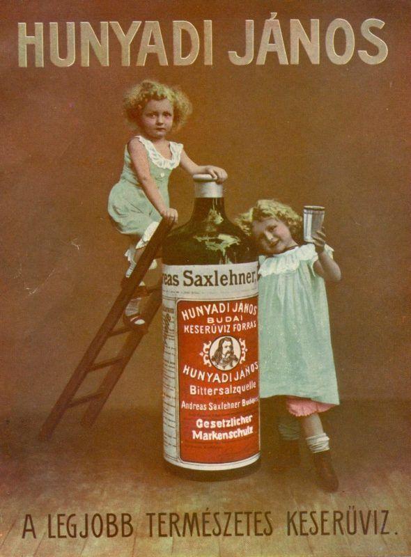 Barna h·ttÈr előtt egy nagy ·sv·nyvizes ¸veg, mellette kÈt kisl·ny, az egyik lÈtr·n m·szik az ¸veg tetejÈre, a m·sik poharat tart a kezÈben. A kÈsőbbi Hunyadi J·nos ·sv·nyvÌz forr·s·t 1862-ben tal·lta meg Bayer J·nos, aki eladta Saxlehner Andr·s posztÛkereskedőnek. Az ˙j tulajdonos korszerű palackozÛ ¸zemet ÈpÌttetett Ès 1877-ben vÈdjegyeztette a Hunyadi J·nos keserűvizet. Az a XX. sz·zad elejÈre vil·ghÌrűvÈ v·lt, k¸lfˆldre is sz·llÌtott·k Ès t˙lÈlte az ·llamosÌt·st Ès a privatiz·ciÛt is.
