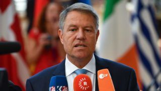 """Romania's President Klaus Werner Iohannis speaks to journalists as he arrives to take part in the last day of the European Union leaders' summit, without Britain, to discuss Brexit and eurozone reforms on June 29, 2018 at the Europa building in Brussels. EU leaders clinched a hard-won migration deal during all-night talks on June 29, that Italy's hardline new premier said meant his country was """"no longer alone"""" in shouldering the responsibility for migrants. / AFP PHOTO / Ben STANSALL"""