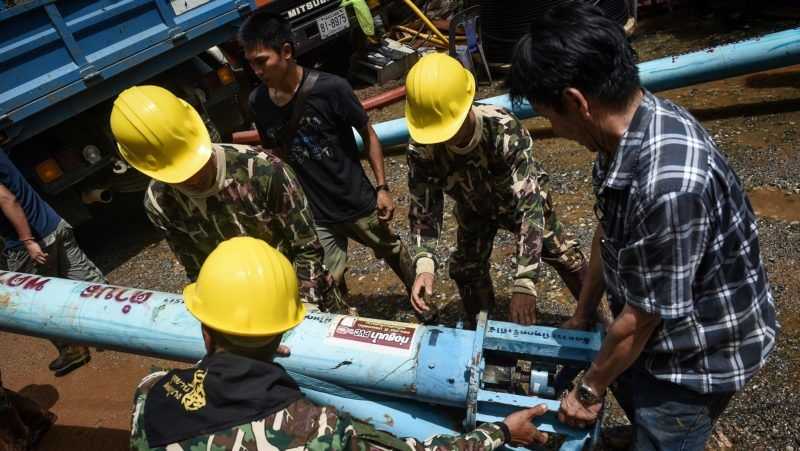 Technicians lift water pumps to the drilling site near Tham Luang cave, at the Khun Nam Nang Non Forest Park in Chiang Rai province on July 1, 2018 as the rescue operation continues for a missing children's football team and their coach.  Twelve Thai boys and their assistant football coach spent their eighth night trapped in a flooded cave, as a round-the-clock search was aided by better weather. / AFP PHOTO / Lillian SUWANRUMPHA