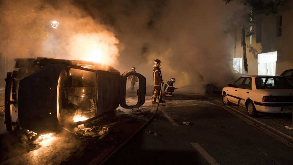 Firefighters work to put out a fire near a burning car in the Malakoff neighborhood of Nantes early on July 4, 2018.  Groups of young people clashed with police in the western French city of Nantes on the night of July 3 after a man was shot dead by an officer during a police check. Cars were burned and a shopping centre partly set alight in the Breil neighbourhood as police confronted young people, some armed with molotov cocktails. / AFP PHOTO / SEBASTIEN SALOM GOMIS