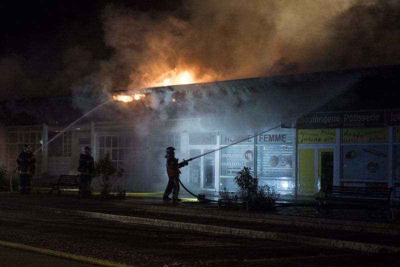 Firefighters work to put out a fire in a building in the Dervallieres neighborhood of Nantes early on July 4, 2018.  Groups of young people clashed with police in the western French city of Nantes on the night of July 3 after a man was shot dead by an officer during a police check. Cars were burned and a shopping centre partly set alight in the Breil neighbourhood as police confronted young people, some armed with molotov cocktails. / AFP PHOTO / SEBASTIEN SALOM GOMIS