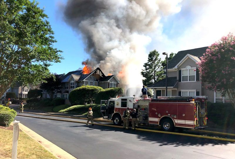 """Emergency crews are on the scene of an helicopter crash in a residential neighborhood at the Bristol Commons apartment complex in Williamsburg, Virginia on July 8 2018. A helicopter crashed into a townhouse complex in the US state of Virginia on Sunday, leaving one person dead and the building ripped apart and damaged by fire, local media said. / AFP PHOTO / WYDaily.com AND Bryan DeVasher / Handout / RESTRICTED TO EDITORIAL USE - MANDATORY CREDIT """"AFP PHOTO / Courtesy of Williamsburg Yorktown Daily/WYDaily.com / Bryan DeVasher """" - NO MARKETING NO ADVERTISING CAMPAIGNS - DISTRIBUTED AS A SERVICE TO CLIENTS"""