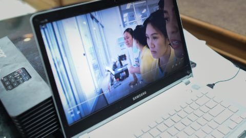 """Local government workers use a laptop to project newly released video footage of the 12 resued """"Wild Boars"""" by Thai government public relations department (PRD) during a press conference in Mae Sai in Chiang Rai district on July 11, 2018. The 12 boys rescued from a Thai cave were sedated and passed on stretchers along the twisting, narrow passageways of the Tham Luang complex, a rescuer said on July 11 as the first footage emerged of an astonishing mission that has captivated the world. / AFP PHOTO / YE AUNG THU"""