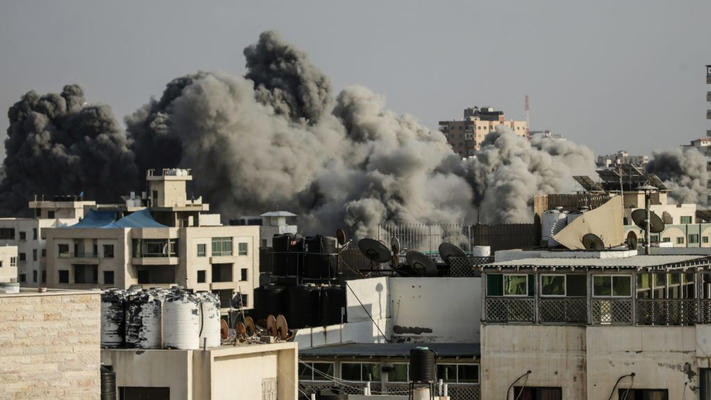 Smoke rises above buildings during an Israeli air strike on Gaza City on July 14, 2018.  Israel's military renewed air strikes targeting Hamas in the Gaza Strip today, following border clashes in which two Palestinians including a teenager were killed and hundreds injured. / AFP PHOTO / MAHMUD HAMS