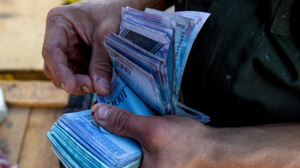 (FILES) In this file photo taken on June 20, 2018 a man counts 1000-Bolivar-bills to buy groceries at the municipal market of Coche, a neighbourhood of Caracas. According to an IMF projection that poses volatile scenarios, inflation in Venezuela would reach 1,000,000% this year, with a single certainty: the dramatic deterioration of living conditions.   / AFP PHOTO / Federico PARRA