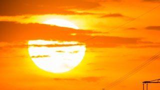 25 July 2018, Germany, Possendorf: The sun sets behind power poles. Photo: Arne Immanuel Bänsch/dpa