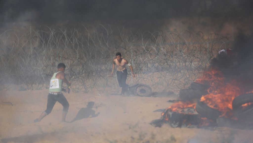 "KHAN YUNIS, GAZA - JULY 06: Palestinian demonstrators burn tires in response to Israeli security forces' intervention during a demonstration held within the ""Great March of Return"" near Israel-Gaza border in Khan Yunis, Gaza on July 06, 2018.   Ashraf Amra / Anadolu Agency"