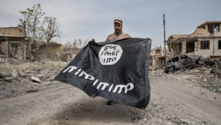 A soldier of the ninth division of the Iraqi Army presents an ISIS flag, which he has found in the debris near the destroyed Jamhuri Hospital in West Mosul. (Photo by Sebastian Backhaus/NurPhoto)