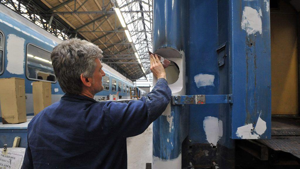 Szolnok, 2013. március 25. Egy dolgozó csiszolja festés előtt az egyik vasúti személykocsi zárlámpájának helyét a szolnoki járműjavítóban 2013. március 25-én. A MÁV-START járműfelújítási programot indított, amelynek során a vasúti személykocsiknak megújul a belső tere a padlóburkolatok és az üléshuzatok cseréjével, az ablakkereteket és az ablakok szigetelését is javítják, és hővédő fóliával vonják be, a falakat pedig antigraffiti réteggel látják el a műhelyekben.MTI Fotó: Máthé Zoltán
