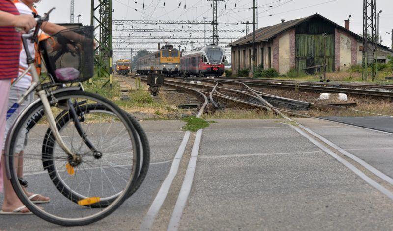 Pusztaszabolcs, 2013. augusztus 24. Három vonat egyszerre indul Pusztaszabolcs állomásról Székesfehérvár, Pécs és Dunaújváros felé, elõtérben a sorompónál várakozó kerékpárosok, a háttérben jobbra a lebontásra ítélt pusztaszabolcsi régi fûtõház épülete 2013. augusztus 24-én. MTI Fotó: Máthé Zoltán