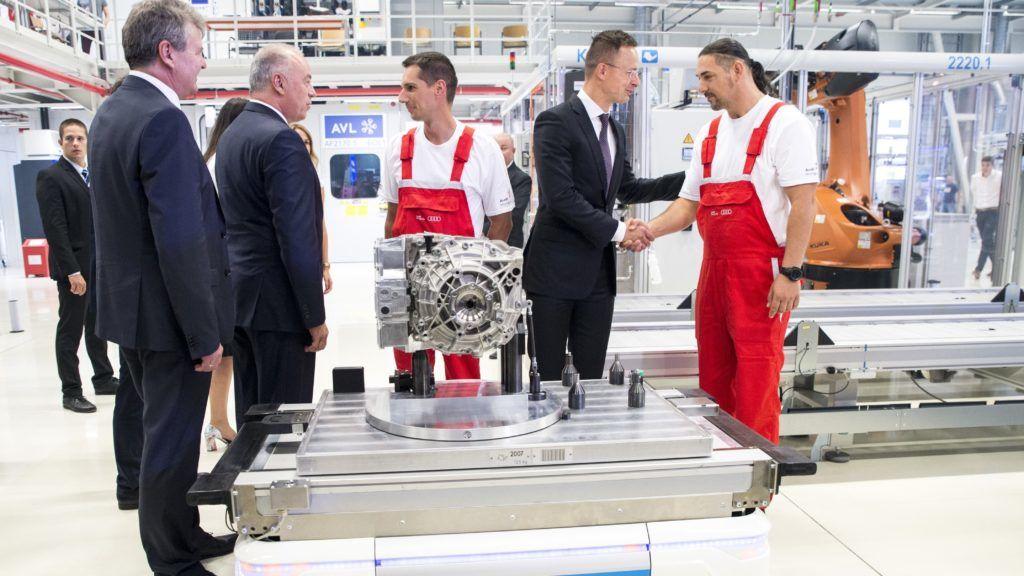 Gyõr, 2018. július 24. Szijjártó Péter külgazdasági és külügyminiszter (j2) kezet fog egy dolgozóval, balról Achim Heinfling, az Audi Hungaria Zrt. igazgatóságának elnöke (b) valamint Peter Kössler, az Audi AG termelésért és logisztikáért felelõs igazgatója (b2) az Audi Hungaria Zrt. elektromos motorokat gyártó üzemében tartott ünnepségen, Gyõrben 2018. július 24-én. A gyárban elindult az elektromos motorok sorozatgyártása. MTI Fotó: Krizsán Csaba