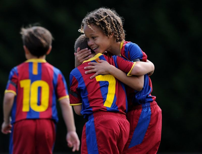 BARCELONA, SPAIN - MAY 15:  Eight-year-old Barcelona youth player Xavi Simons (R) celebrates a goal with a teammate againts Llongueras on one of the pitches at the Joan Camper training ground on May 15, 2011 in Barcelona, Spain. Every weekend various teams of Barcelona youth players play in matches with the hope of one day making it to the top.  (Photo by Jasper Juinen/Getty Images)