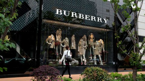 SHANGHAI, CHINA - APRIL 25:  A woman walks in front of Burberry's new flagship store on April 25, 2014 in Shanghai, China.  (Photo by Kevin Lee/Getty Images)