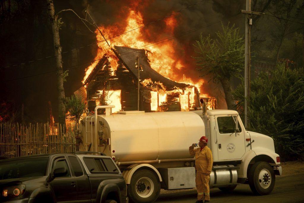 Shasta, 2018. július 27. Lángoló épület elõterében iszik egy férfi egy lajtos kocsinál a kaliforniai erdõtüzek sújtotta Shastában 2018. július 26-án. A két hete pusztító tûz a San Franciscótól 300 kilométerre, keletre fekvõ El Portal település térségében, a Sierra Nevada hegységben ütötte fel a fejét. Az oltást a száraz, meleg idõ nehezíti. (MTI/AP/Noah Berger)