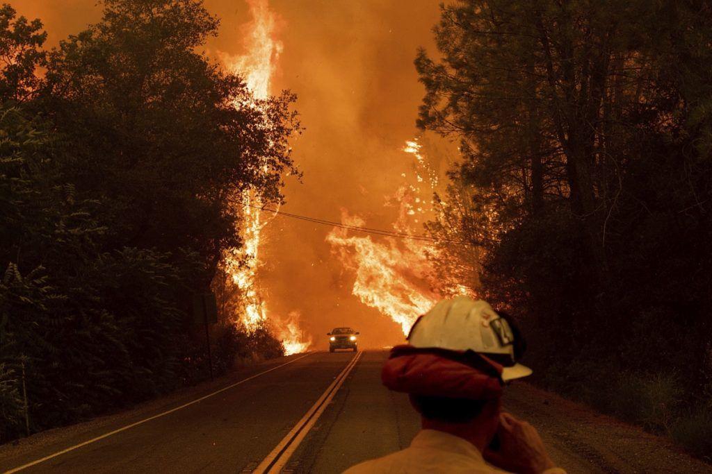 Shasta, 2018. július 27. Tûzoltó néz egy közeledõ autót a lángoló növényzetettel övezett útak egyikén a kaliforniai erdõtüzek sújtotta Shastánál 2018. július 26-án. A két hete pusztító tûz a San Franciscótól 300 kilométerre, keletre fekvõ El Portal település térségében, a Sierra Nevada hegységben ütötte fel a fejét. Az oltást a száraz, meleg idõ nehezíti. (MTI/AP/Noah Berger)