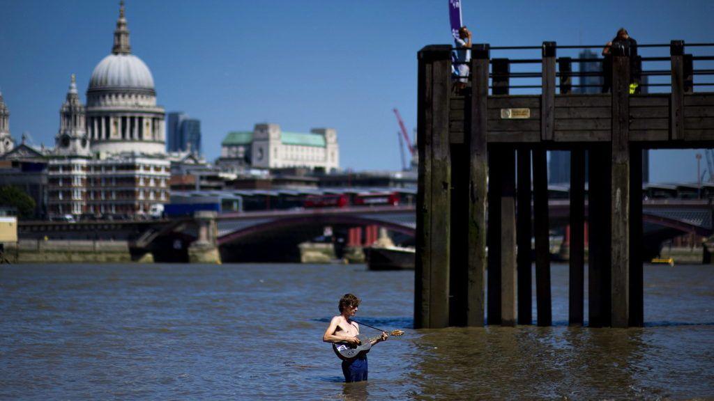 London, 2013. július 19. Egy férfi gitározik a Temze folyó vizében London déli részén 2013. július 19-én. A brit meteorológiai szolgálat hármas fokozatú hõségriadót rendelt el Anglia délnyugati részén, miután 2006. óta nem volt arra példa, hogy hat egymást követõ napon 30 Celsius fok felett lett volna a hõmérséklet. (MTI/EPA/Bogdan Maran)