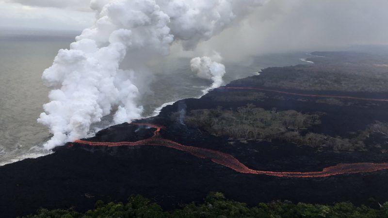 Keleti Riftzóna, 2018. május 25. Az amerikai földtani intézet (USGS) által közreadott légi felvételen  gõzfüggöny csap fel a vízpartról, amint a Kilauea tûzhányó lávafolyama beleömlik a Csendes-óceánba a Hawaii szigetén fekvõ Keleti Riftzónában 2018. május 24-én. A világ egyik legaktívabb tûzhányójának számító Kilauea vulkáni tevékenysége május 3. óta tart. A környékén kötelezõ kitelepítés van érvényben, a lávafolyam eddig 44 házat pusztított el. Jelenleg tilos az óceánban való fürdõzés a térségben, mert a láva és a víz találkozásakor veszélyes sósav keletkezhet, a vulkán pedig egyre nagyobb mértékben lövell ki szintén mérgezõ kén-dioxidot. (MTI/EPA/USGS/M. Patrick)