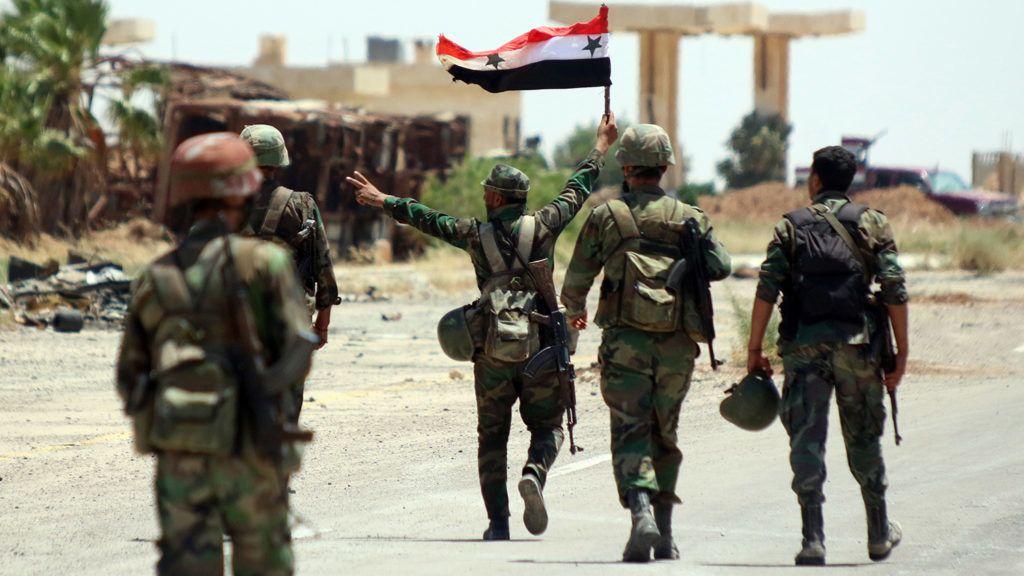 Naszíb, 2018. június 8.Szíriai kormánykatona az ország zászlaját viszi a naszíbi határátkelőnél, a Jordániával szomszédos délnyugat-szíriai Deraa tartományban 2018. július 7-én. A szíriai kormányerők egy nappal korábban visszafoglalták a felkelőktől a stratégiai jelentőségű átkelőt. (MTI/EPA/Juszef Badaui)