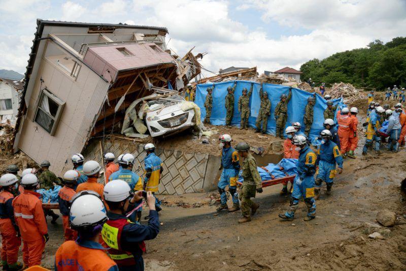 Kumano, 2018. július 9. Romba dõlt ház mellett viszik egy áldozat holttestét mentõk a Hirosima prefektúrabeli Kumanóban 2018. július 9-én. A heves esõzések elõidézte áradások és földcsuszamlások miatt mintegy száz ember életét vesztette, hatvannyolcat eltûntként tartanak nyilván Japán nyugati és közéspõ részén. (MTI/EPA/Jiji Press)  *** Local Caption *** malý vrtu¾ník