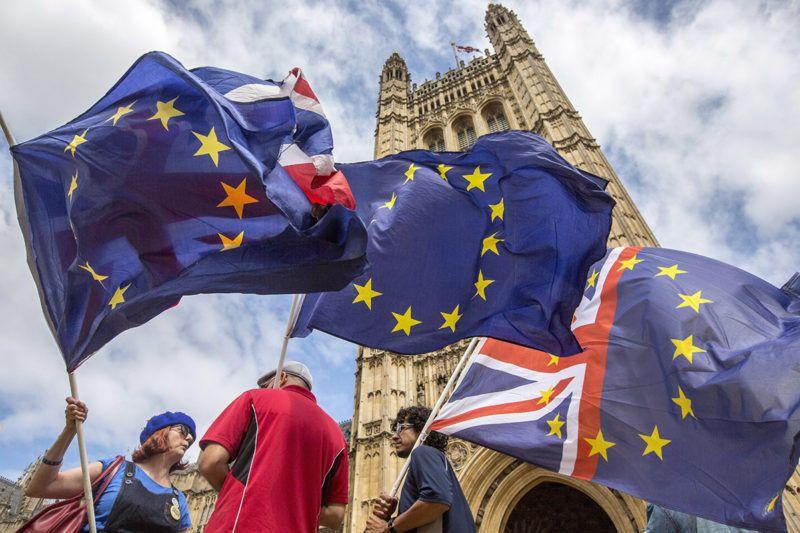 London, 2018. július 10.A Brexit-folyamat leállítását követelő tüntetők uniós zászlókat lengetnek a parlament épülete előtt Londonban 2018. július 10-én. (MTI/EPA/Rick Findler)