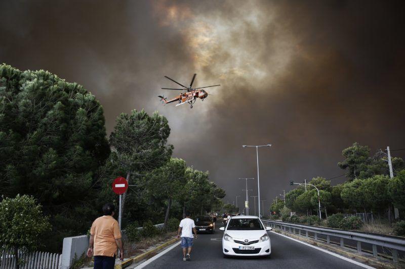 Athén, 2018. július 23. A görög fõvárostól északkeletre pusztító erdõtûz ellen küzdõ tûzoltó-helikopter egy athéni külvároson át húzódó autópálya fölött 2018. július 23-án. Az Athén és Korinthosz közötti tengerparti település, Kineta melletti Geraneia hegyen keletkezett tûz után újabb erdõtûz lobbant fel a fõvárostól északkeletre fekvõ Penteli-hegyen. (MTI/EPA/Alexandrosz Vlahosz)