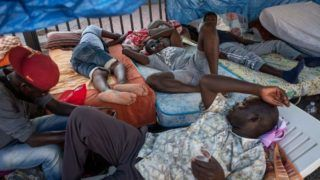 """ROME, ITALY - JULY 9: Migrants and refugees stay outside a building after being evicted 4 days ago by Italian Police, on July 9, 2018 in Rome, Italy. About 120 African migrants were evicted from a building managed until 2015 by a cooperative, """"La Casa della Solidarietà"""", involved in """"Mafia Capitale"""". (Photo by Antonio Masiello/Getty Images)"""