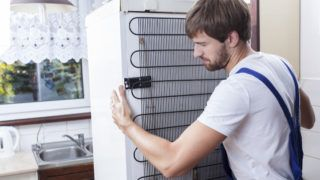 Handyman trying to move a fridge at house