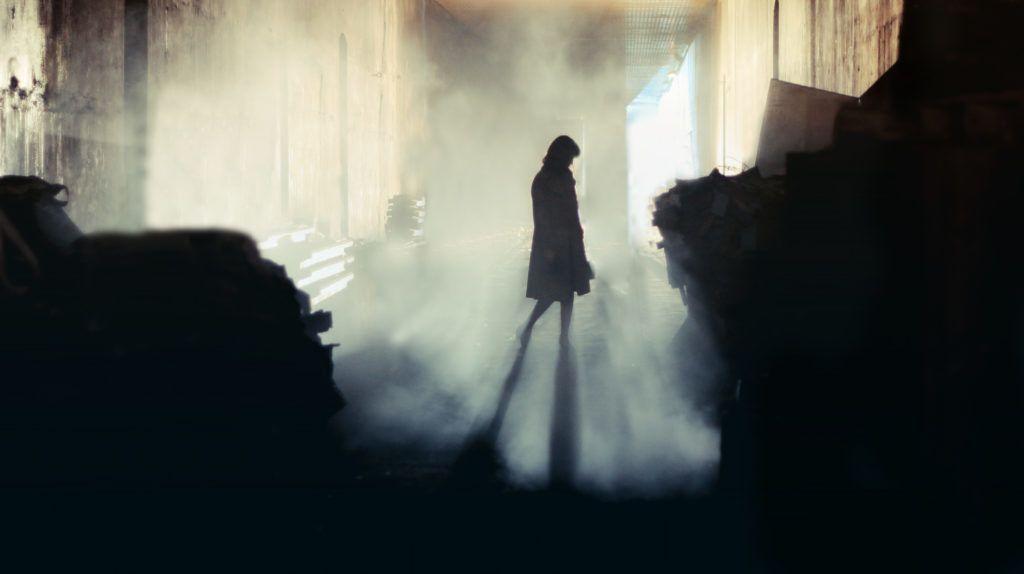 A lone wonan stands in a misty underground tunnel