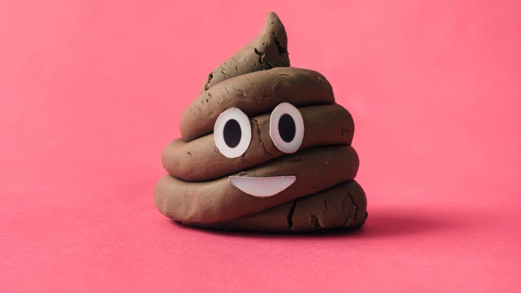 Poop emoticon on pink background.