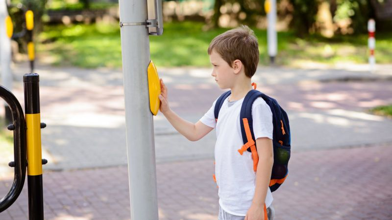 Little schoolboy with backpack pressing a button on traffic lights . Road to school