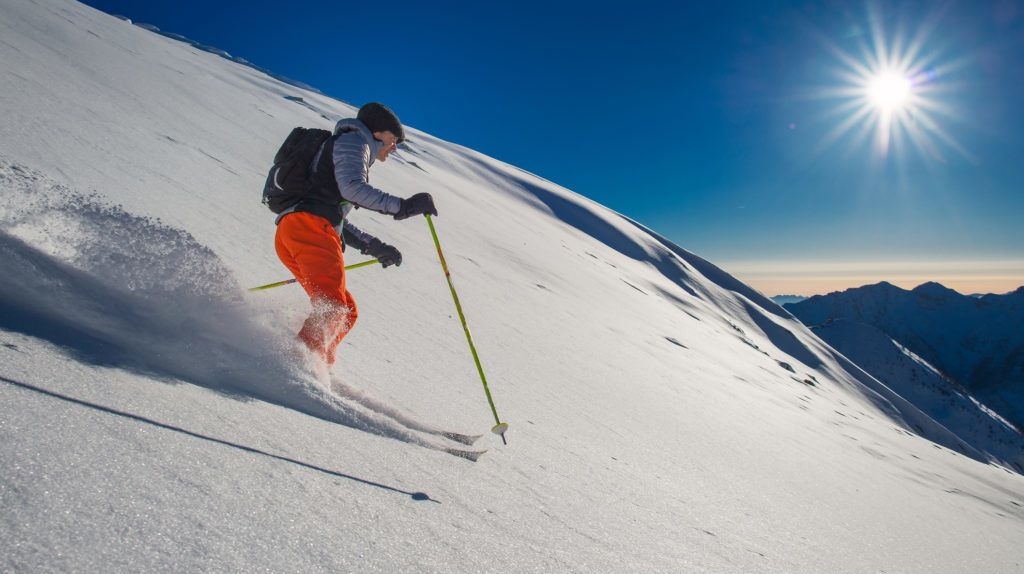 Backcountry skier in fresh snow in beautiful sunny day