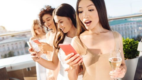 Unexpected message. Happy beautiful surprised woman holding her cell phone and reading a message while standing together with her friends