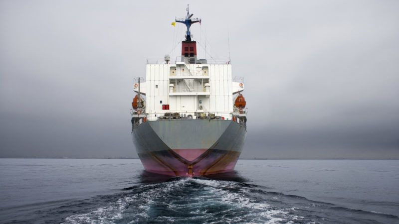 Stern of a grey and pink cargo ship.