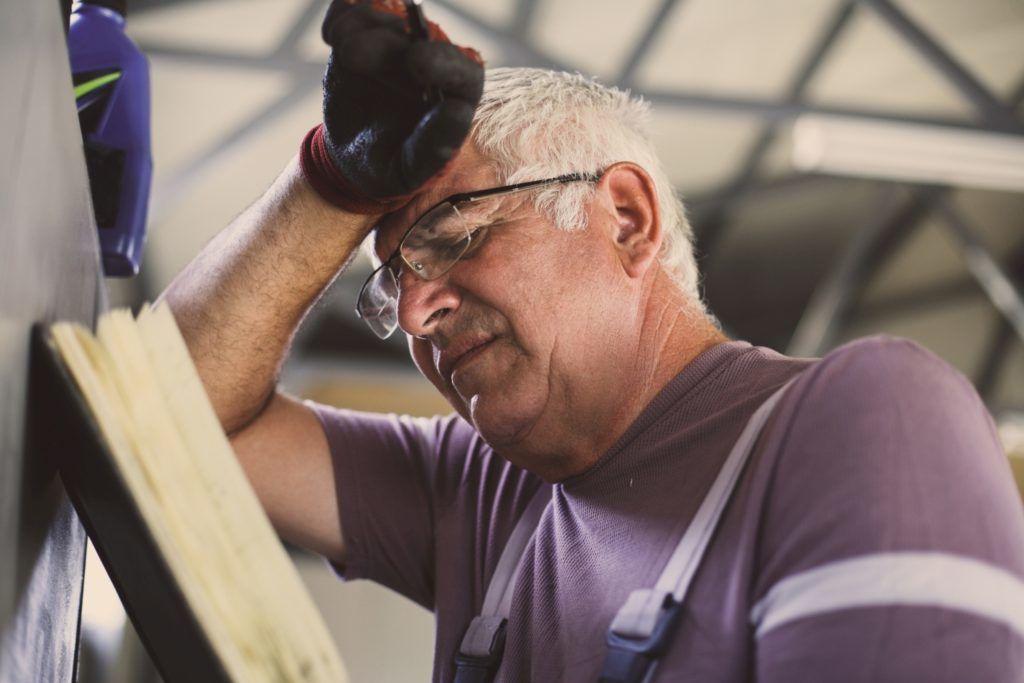 Senior man in workshop. Worried  man reading his planner.