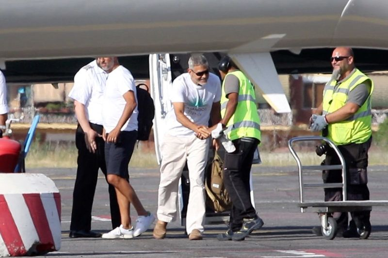 """EXCLUSIVE: *NO WEB UNTIL 6.30pm PST JULY 15* George Clooney smiles but is in pain as he arrives in Rome after his scooter accident. Clooney was catapulted off his scooter on the Italian island of Sardinia when he crashed into a Mercedes that turned suddenly into his lane. The Hollywood heart throb walked gingerly as he slowly made his way off his private jet Sunday after it touched down in Rome, where he's set to resume filming for his new Hulu series """"Catch-22. 15 Jul 2018 Pictured: George Clooney  in Rome after the crash. Photo credit: MEGA  TheMegaAgency.com +1 888 505 6342 July  , 2018 *** Local Caption *** MEGA252756_001"""