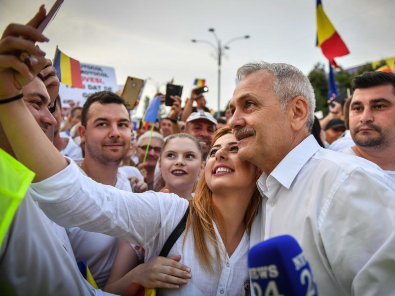 Romania's social democratic party (PSD) leader Liviu Dragnea (2nd R) poses for a selfie with a supporter at the Piata Victoriei square, next to the Romanian Government headquarters, during a support meeting organized by the PSD (Social Democrat Party) ruling party in Bucharest, June 9, 2018. From busing supporters to Bucharest to mass mailings of party slogans, Romania's left-wing government was pulling out all the stops for the demonstration against the country's own judiciary. / AFP PHOTO / Daniel MIHAILESCU