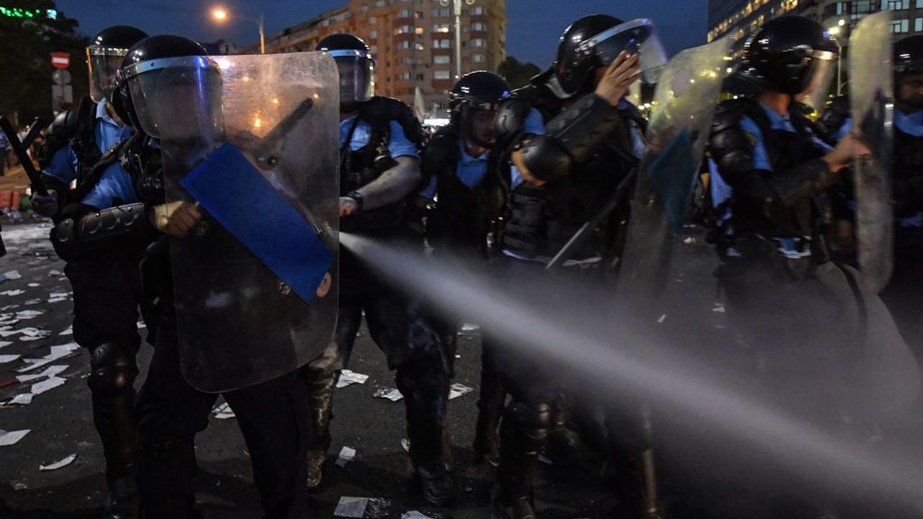 """Romanian anti riot police clash with protesters during a demonstration in front of the Romanian Government headquarters in Bucharest August 10, 2018, to protest against the government.Romanian police used tear gas and pepper spray to quell anti-corruption protesters in Bucharest on August 10, 2018, as tens of thousands called on the leftwing government to resign. Local media said between 30,000 to 50,000 people turned out for the protest, included many Romanian expatriates who returned home especially to show their anger at the levels of official corruption.The crowd chanted """"resign"""" and """"thieves"""" as they assembled in a central square outside the main government building. / AFP PHOTO / Daniel MIHAILESCU"""