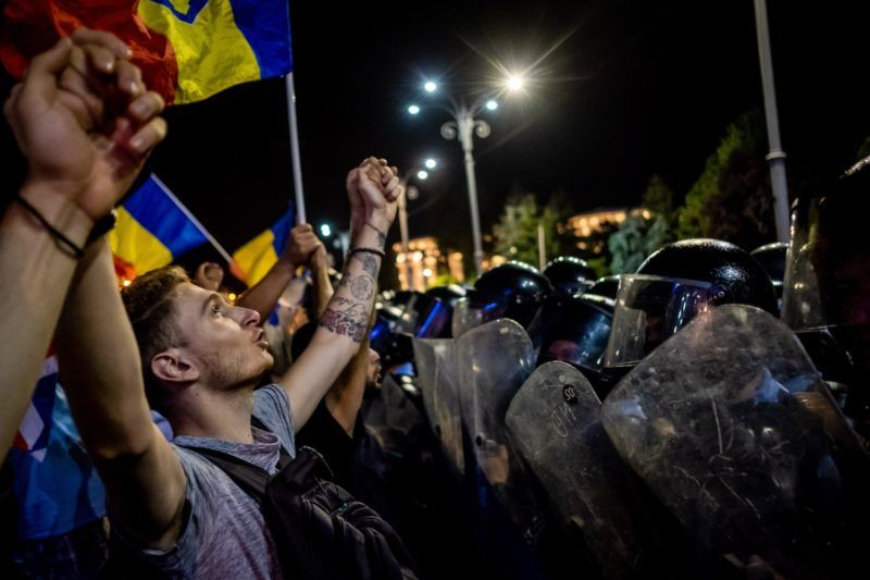 Romanians take part in a demonstration in front of the Romanian Government headquarters, in Bucharest August 10, 2018, to protest against the government. Romanian police used water cannon and tear gas to disperse anti-corruption protesters in Bucharest after tens of thousands rallied to call on the leftwing government to resign. Local media said between 50,000 to 80,000 people turned out for the protest, including many Romanian expatriates who returned home to show their anger at the graft in one of the EU's most corruption-plagued members.  / AFP PHOTO / Andrei PUNGOVSCHI