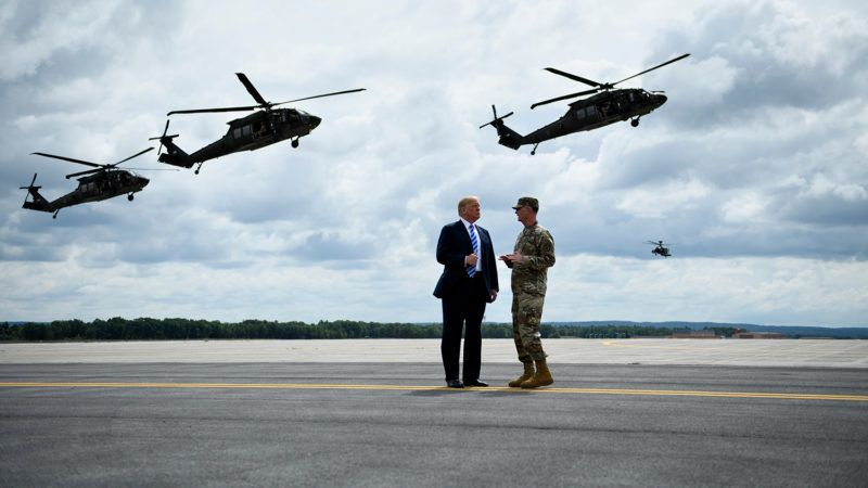 (FILES) In this file photo taken on August 13, 2018 US President Donald Trump (L) watches an air assault exercise with Army Major General Walter Piatt at Fort Drum, New York.A military parade ordered by US President Donald Trump for later this year has been postponed until at least 2019, a defense official said Thursday, following reports the cost had soared to over $90 million. / AFP PHOTO / Brendan Smialowski