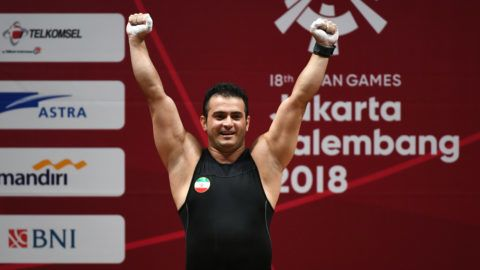 Sohrab Moradi of Iran celebrates after breaking the world record in the men's 94kg class weightlifting event at the 2018 Asian Games in Jakarta on August 25, 2018. / AFP PHOTO / Bay ISMOYO