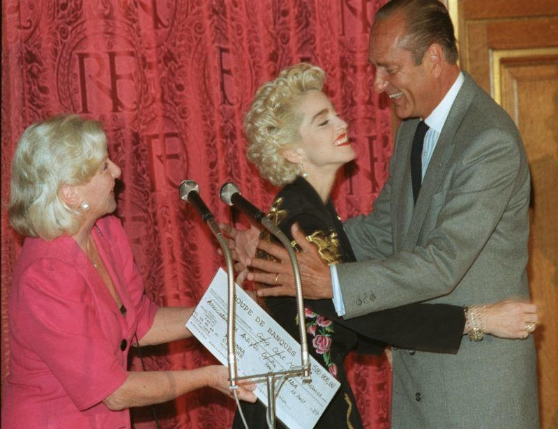 French neo-Gaullist Prime Minister and Paris Mayor Jacques Chirac hugs warmly Italian-born US-pop idol Madonna 28 August 1987 at Paris City Hall during a charity event for AIDS victims. At left, French popular singer and dancer, Line Renaud. AFP PHOTO JEAN-LOUP GAUTREAU  / AFP PHOTO / JEAN-LOUP GAUTREAU