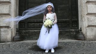 A young actress plays the role of Giorgia, 10, forced to marry Paolo, 47, during a happening organised by Amnesty International to denounce child marriage, on October 27, 2016 in Rome.  / AFP PHOTO / GABRIEL BOUYS