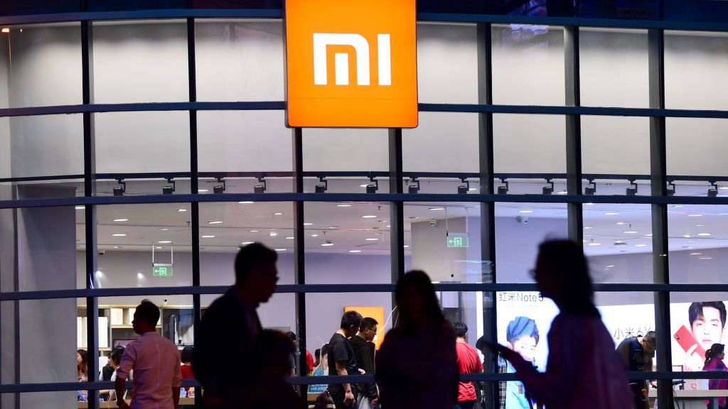 """--FILE--Pedestrians walk past a Xiaomi store in Shenyang city, northeast China's Liaoning province, 13 May 2018.  The first Mi Store of Chinese technology giant Xiaomi in Vietnam's Hanoi capital did not officially opened until 10 a.m on Saturday (13 May 2018), but hundreds of Vietnamese people flocked here and made two parallel long queues as early as from 3 a.m. local time. """"I queued up here from 3 a.m. this morning. I've already used a Redmi Note 3 Pro and a 10,000-mAh Mi power bank for two years. They're still running very well, so I won't buy the latest model, Redmi Note 5 Plus, but I want to buy a portable Wi-Fi device,"""" Dao Duy Hoa, a fourth-year-student at the Hanoi Academy of Theater and Cinema, told Xinhua on Saturday when he topped one of the two long queues."""
